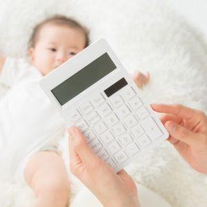 赤ちゃんの傍で計算機を持つ女性