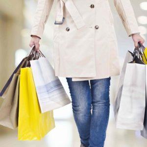 デパートでたくさんの買い物袋を手に歩く女性