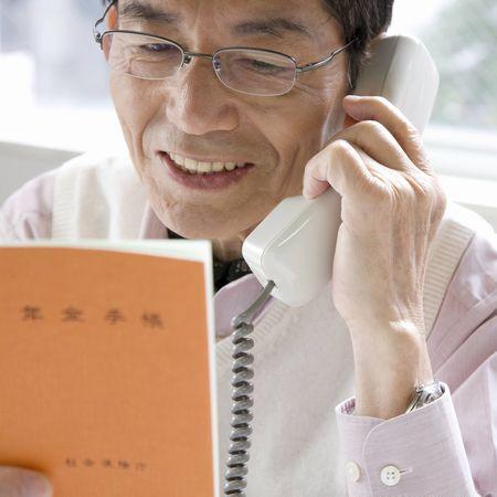 年金手帳を見ながら電話をかける高齢男性