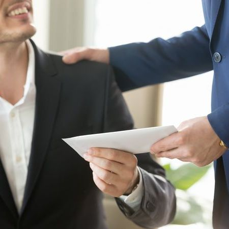 上司から封筒を手渡されたスーツ姿の男性