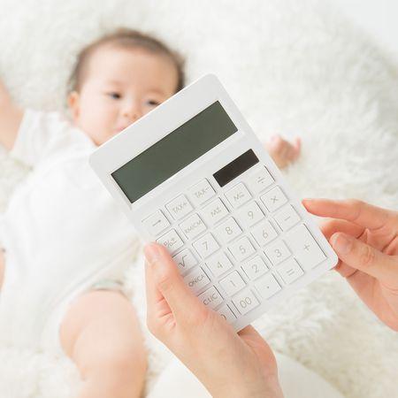 赤ちゃんの前で電卓を持つ手