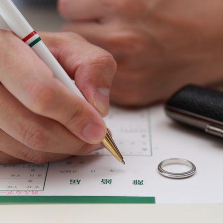 指輪と印鑑を机の上に置いて離婚届に記入する人