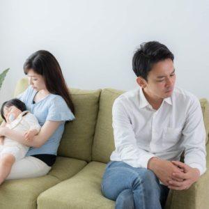 ソファで赤ん坊を抱く妻と背を向ける夫