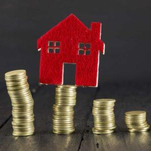 積み上げられた硬貨の上に載っている住宅の模型