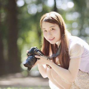 カメラを持って微笑む若い女性