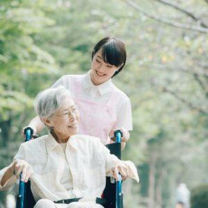 車椅子に座る高齢女性と、車椅子を押す介護士の女性