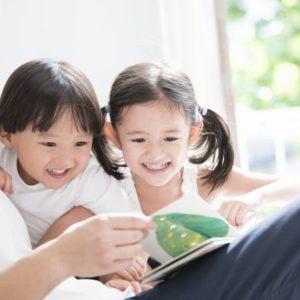 絵本を読んでもらっている幼い女の子と男の子