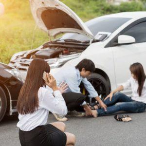 交通事故によるケガ人の応急処置や救急通報のために電話をかけている様子