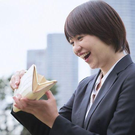 笑顔で財布の中を除く、スーツ姿の若い女性